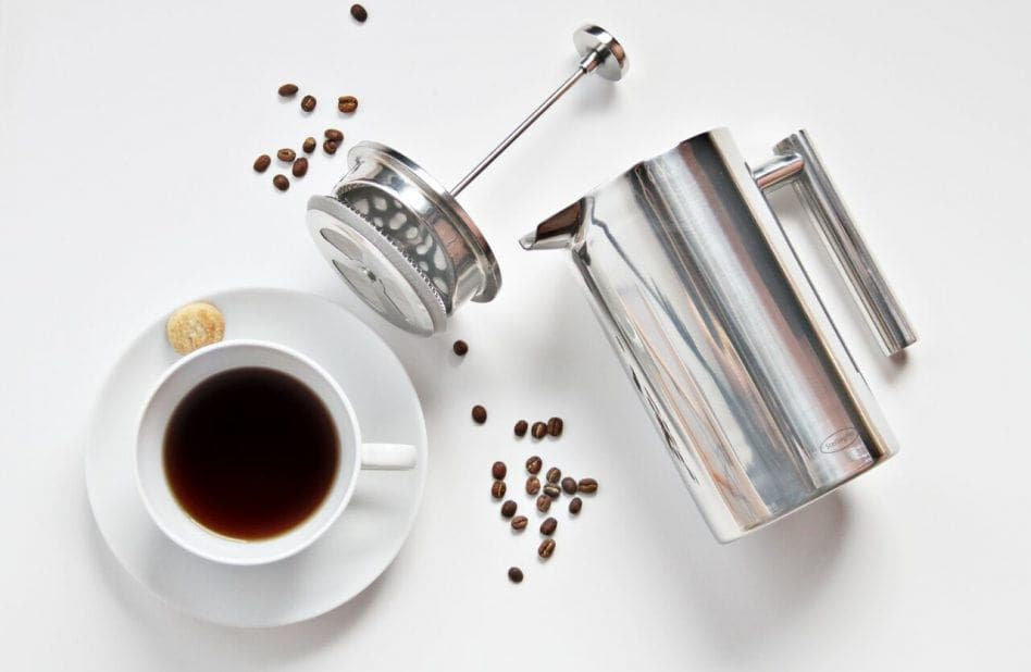 Cup of coffee next to French Press